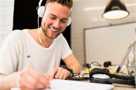 Happy young businessman wearing headphones while writing in book at creative office Stock Photo - Premium Royalty-Free, Code: 698-07635558
