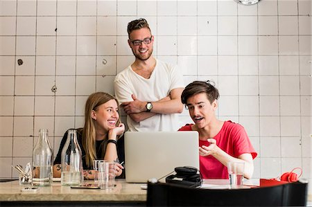 Young business people discussing over laptop in creative office Stock Photo - Premium Royalty-Free, Code: 698-07635564