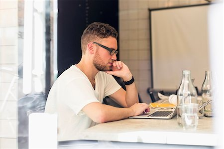 Side view of young businessman using laptop in creative office Stock Photo - Premium Royalty-Free, Code: 698-07635562