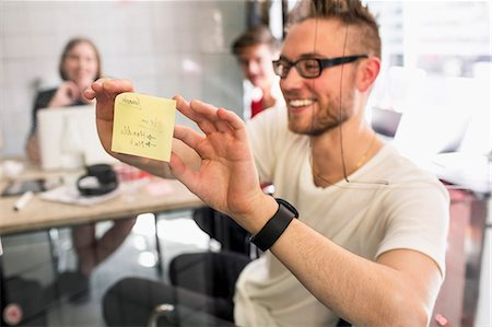 self adhesive note - Young businessman sticking adhesive note on transparent glass with colleagues at background in new office Stock Photo - Premium Royalty-Free, Code: 698-07635577