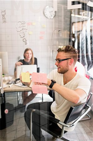 Young businessman writing ideas on adhesive notes with female colleague in background at new office Stock Photo - Premium Royalty-Free, Code: 698-07635578