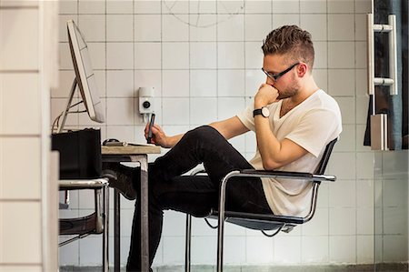 small business owners - Side view of young businessman at computer desk in new office Stock Photo - Premium Royalty-Free, Code: 698-07635586