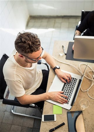 High angle view of young businessman using laptop in creative office Stock Photo - Premium Royalty-Free, Code: 698-07635594
