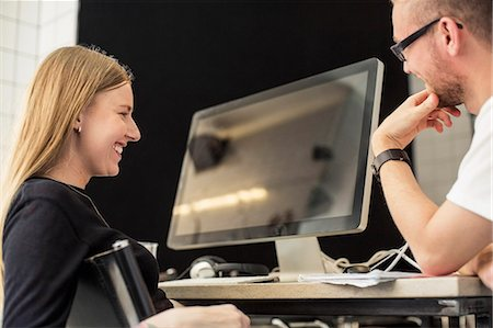 Young businessman and businesswoman looking at computer monitor in creative office Stock Photo - Premium Royalty-Free, Code: 698-07635590