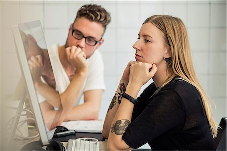 Young businessman and businesswoman looking at computer monitor in creative office Stock Photo - Premium Royalty-Free, Code: 698-07635592