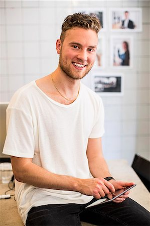 small business owners - Portrait of happy young businessman using digital tablet in new office Stock Photo - Premium Royalty-Free, Code: 698-07635606