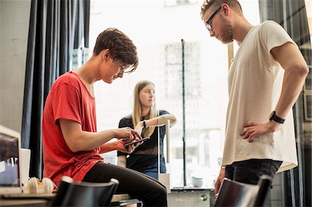 Young businessmen using digital tablet with female colleague in background at new office Stock Photo - Premium Royalty-Free, Code: 698-07635601
