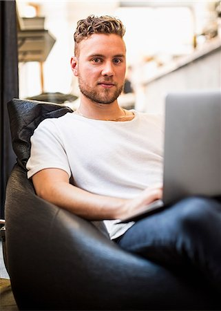 Portrait of confident young businessman using laptop while sitting on bean bag chair in new office Stock Photo - Premium Royalty-Free, Code: 698-07635616