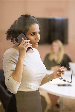 Businesswoman answering smart phone in creative office Stock Photo - Premium Royalty-Free, Code: 698-07635636