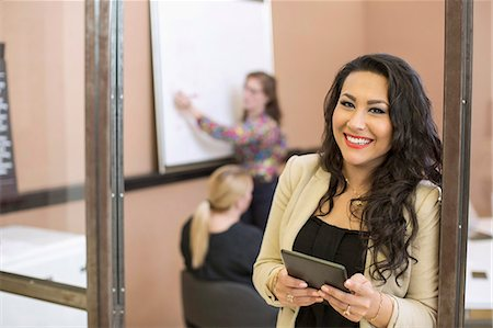 Portrait of happy businesswoman with digital tablet standing at board room entrance in office Stock Photo - Premium Royalty-Free, Code: 698-07635640