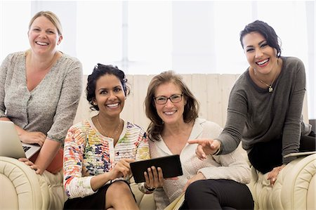 Portrait of happy businesswomen on sofa in creative office Stock Photo - Premium Royalty-Free, Code: 698-07635653