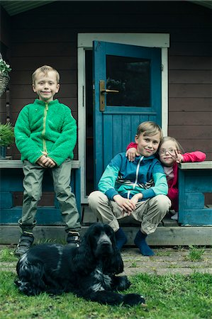 Portrait of siblings with dog sitting on porch Stock Photo - Premium Royalty-Free, Code: 698-07635679