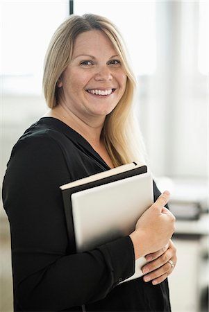 female - Portrait of happy businesswoman holding book and digital tablet in creative office Stock Photo - Premium Royalty-Free, Code: 698-07635672