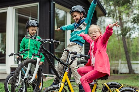 Portrait of girl with arms outstretched riding bicycle with brothers in lawn Stock Photo - Premium Royalty-Free, Code: 698-07635685