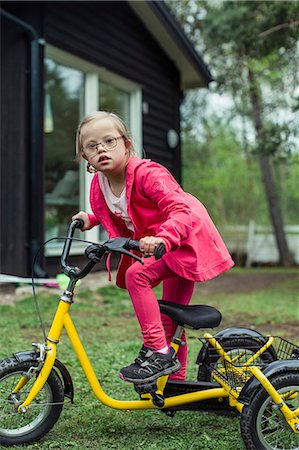 Portrait of girl with down syndrome riding bicycle in lawn Stock Photo - Premium Royalty-Free, Code: 698-07635686