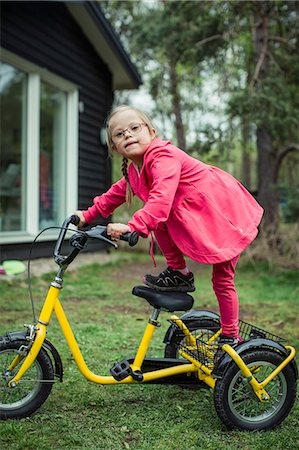 Portrait of girl with down syndrome balancing on bicycle in lawn Stock Photo - Premium Royalty-Free, Code: 698-07635687