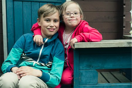 Portrait of handicapped girl with arm around brother sitting on porch Stock Photo - Premium Royalty-Free, Code: 698-07635680