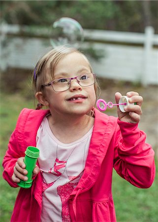 Girl playing with bubble wand in lawn Stock Photo - Premium Royalty-Free, Code: 698-07635681