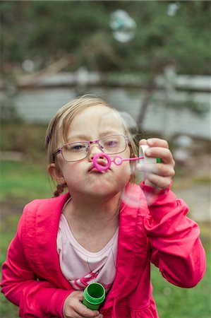 Girl blowing bubbles in lawn Stock Photo - Premium Royalty-Free, Code: 698-07635682