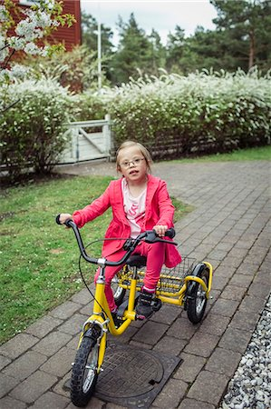 Portrait of girl with down syndrome riding bicycle in lawn Stock Photo - Premium Royalty-Free, Code: 698-07635683