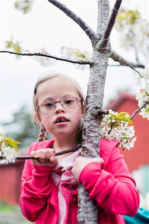 Portrait of girl with down syndrome holding tree branch in yard Stock Photo - Premium Royalty-Free, Code: 698-07635695