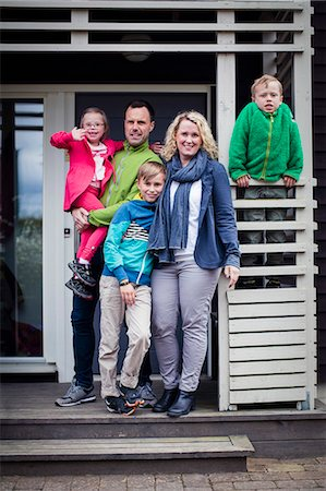 Portrait of happy family standing at porch Stock Photo - Premium Royalty-Free, Code: 698-07635699