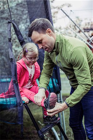 Father assisting handicapped daughter in wearing shoes at lawn Stock Photo - Premium Royalty-Free, Code: 698-07635692