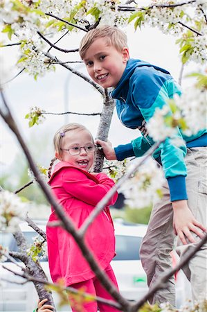 Portrait of boy playing with sister on tree branch Stock Photo - Premium Royalty-Free, Code: 698-07635693