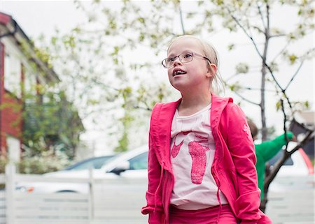 Thoughtful girl with down syndrome looking away while standing in lawn Stock Photo - Premium Royalty-Free, Code: 698-07635706