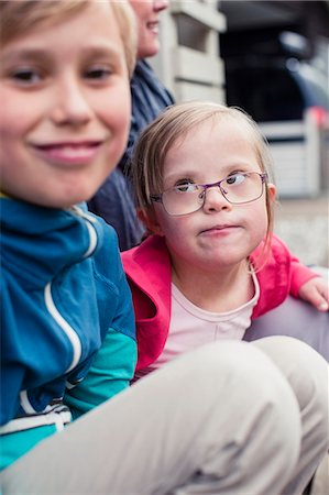 Girl with down syndrome looking at brother outdoors Stock Photo - Premium Royalty-Free, Code: 698-07635707