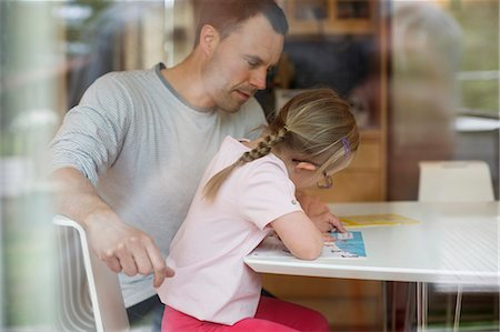 Father assisting handicapped girl in studies at table Stock Photo - Premium Royalty-Free, Code: 698-07635709