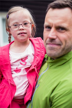 Portrait of girl with down syndrome carried by father Stock Photo - Premium Royalty-Free, Code: 698-07635700