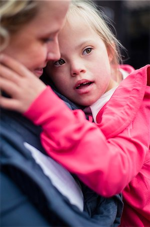Girl with down syndrome carried by mother Stock Photo - Premium Royalty-Free, Code: 698-07635701