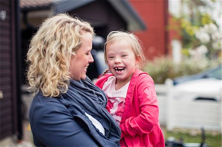 Portrait of girl with mother laughing in yard Stock Photo - Premium Royalty-Free, Code: 698-07635703