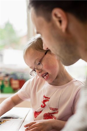 Girl with down syndrome studying by father at home Stock Photo - Premium Royalty-Free, Code: 698-07635716