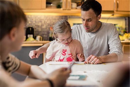 Father teaching daughter with son in foreground at home Stock Photo - Premium Royalty-Free, Code: 698-07635718