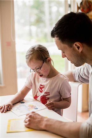 Father assisting handicapped girl in studying at home Stock Photo - Premium Royalty-Free, Code: 698-07635712