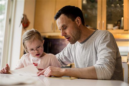 Father assisting handicapped daughter in studying at home Stock Photo - Premium Royalty-Free, Code: 698-07635713