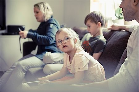 Portrait of handicapped girl sitting with family on sofa at home Stock Photo - Premium Royalty-Free, Code: 698-07635729