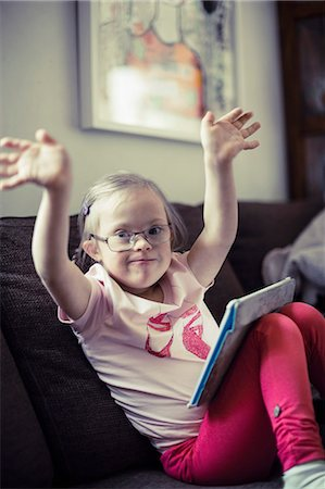 Portrait of handicapped girl with digital tablet raising arms on sofa Stock Photo - Premium Royalty-Free, Code: 698-07635734