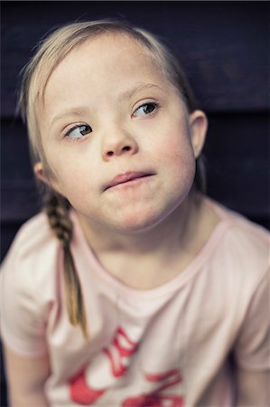 Thoughtful girl with down syndrome looking away Stock Photo - Premium Royalty-Free, Code: 698-07635738