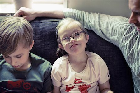 Girl with down syndrome looking at father by brother on sofa Stock Photo - Premium Royalty-Free, Code: 698-07635733