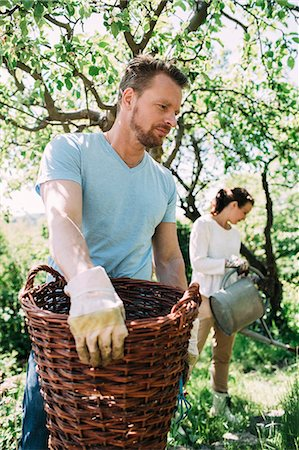 Man carrying wicker basket with woman gardening in background at yard Stock Photo - Premium Royalty-Free, Code: 698-07812946