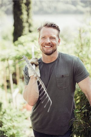 Happy man looking away while carrying gardening fork on shoulder at yard Stock Photo - Premium Royalty-Free, Code: 698-07812957
