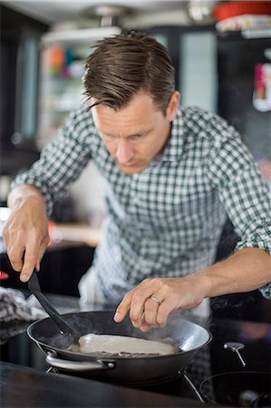 Man cooking fish in kitchen Stock Photo - Premium Royalty-Free, Code: 698-07812972