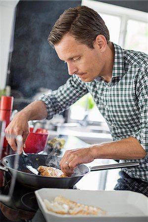 Man preparing fish in kitchen Stock Photo - Premium Royalty-Free, Code: 698-07812973