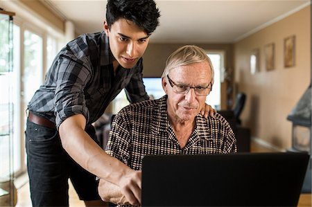 Grandson assisting grandfather in using laptop at home Stock Photo - Premium Royalty-Free, Code: 698-07812984