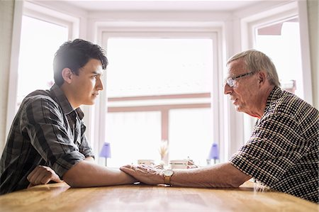 Side view of grandfather consoling grandson at table Stock Photo - Premium Royalty-Free, Code: 698-07812987