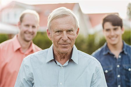 Portrait of confident senior man with son and grandson standing in yard Stock Photo - Premium Royalty-Free, Code: 698-07812999