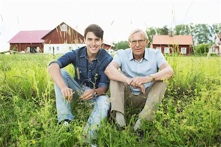 Full length portrait of grandfather and grandson sitting on grassy field Stock Photo - Premium Royalty-Free, Code: 698-07813006